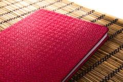 Taccuino di cuoio rosso sulla stuoia di bambù Fotografia Stock Libera da Diritti