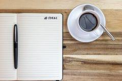 Taccuino di idee sullo scrittorio con un caffè fotografia stock