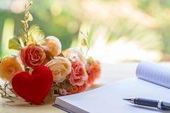 Taccuino e cuori in bianco con il fiore sulla tavola di legno immagini stock libere da diritti