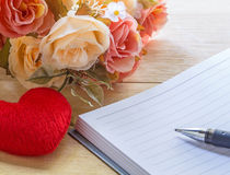 Taccuino e cuori in bianco con il fiore sulla tavola di legno fotografia stock libera da diritti