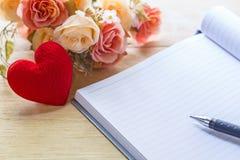 Taccuino e cuori in bianco con il fiore sulla tavola di legno, biglietto di S. Valentino fotografia stock