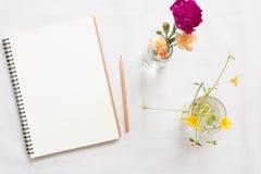 Taccuino e fiore in bianco Fotografie Stock