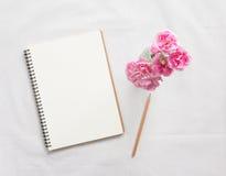 Taccuino e fiore in bianco Immagine Stock