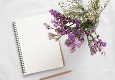 Taccuino e fiore in bianco Immagini Stock
