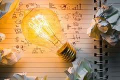 Taccuino e lampadina con il grafico del disegno Fotografia Stock