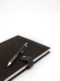 Taccuino e matita di Brown su fondo bianco Immagini Stock
