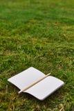 Taccuino e matita sull'erba immagine stock
