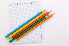 Taccuino e matite colorate su un fondo bianco Fotografia Stock Libera da Diritti