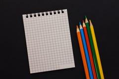 Taccuino e matite colorate su un fondo nero Fotografia Stock Libera da Diritti