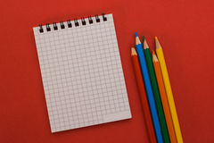 Taccuino e matite colorate su un fondo rosso Fotografia Stock Libera da Diritti