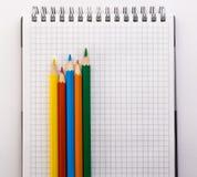 Taccuino e matite colorate su un primo piano bianco del fondo Fotografie Stock