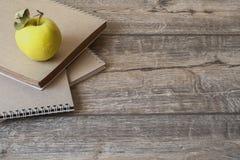 Taccuino e mela della scuola su fondo di legno immagine stock