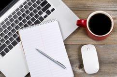 Taccuino e penna in bianco con il computer portatile sul desktop dell'ufficio Immagine Stock