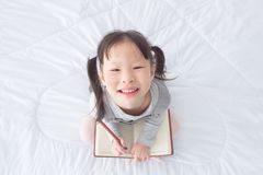 Taccuino e sorrisi della tenuta della bambina sul letto Immagine Stock Libera da Diritti