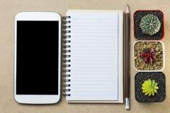 Taccuino e telefono cellulare con la matita ed il cactus del topview sulla fronte Fotografie Stock