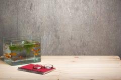 Taccuino e vetri del carro armato di pesce sulla tavola di legno Fotografia Stock