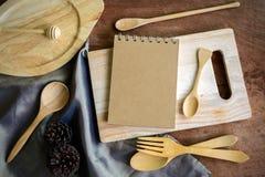 Taccuino ed utensile di legno in cucina su vecchio fondo di legno Fotografia Stock Libera da Diritti