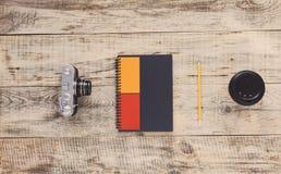 Taccuino, macchina fotografica, tazza di caffè, matita sui bordi di legno anziani Vista da sopra Stile dei pantaloni a vita bassa Fotografia Stock
