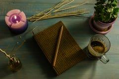 Taccuino, matita, candele profumate, oli essenziali, rami di albero, piccoli alberi in vasi, tazze di caffè Su una tabella di leg Fotografie Stock Libere da Diritti
