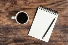 Taccuino, matita e caffè in bianco aperti su un fondo di legno scuro Disposizione piana con lo spazio della copia fotografia stock