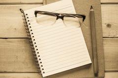 Taccuino, matita ed occhiali sulla tavola di legno Immagine Stock