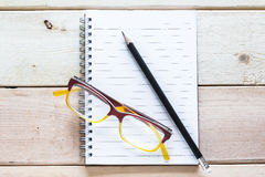 Taccuino, matita ed occhiali sulla tavola di legno Immagine Stock Libera da Diritti