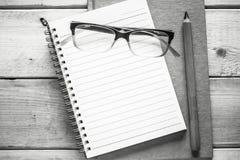 Taccuino, matita ed occhiali sulla tavola di legno Fotografia Stock