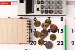 Taccuino, monete, calendario, calcolatore e matita su una tavola Fotografia Stock Libera da Diritti