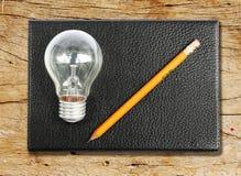 Taccuino nero con il cil giallo della penna e la lampadina Fotografie Stock