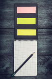 Taccuino nero con uno strato in una gabbia con la matita e le note appiccicose colorate su un fondo rustico di legno, vista super immagine stock