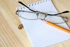 Taccuino, occhiali e matita Fotografie Stock