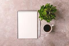 Taccuino, penna, albero di bambù e caffè workplace Vista superiore fotografia stock