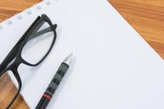 Taccuino, penna e vetri Immagine Stock
