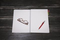 Taccuino, penna e vetri bianchi su un fondo di legno nero Fotografia Stock