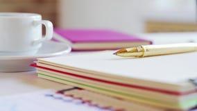 Taccuino, penna, tazza di caffè ed altri accessori sullo scrittorio Posto di lavoro di un uomo d'affari stock footage