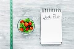 Taccuino per il piano di dieta, l'insalata ed il nastro di misurazione su derisione di legno grigia di vista del piano d'appoggio Fotografia Stock Libera da Diritti