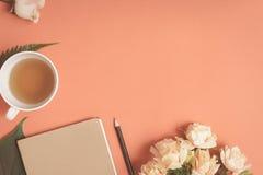 Taccuino piano e rosa di disposizione disposti su uno scrittorio rosso Immagini Stock Libere da Diritti