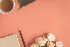 Taccuino piano e rosa di disposizione disposti su uno scrittorio rosso Fotografia Stock Libera da Diritti
