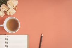Taccuino piano e rosa di disposizione disposti su uno scrittorio rosso Immagini Stock