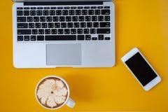 Taccuino posto piano disposto su una tavola di colore con una tazza di caff?, sulla tavola della scrivania con il computer portat fotografia stock