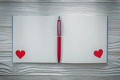 Taccuino pulito rosso della penna a sfera dei cuori su istruzione di legno del bordo Fotografie Stock