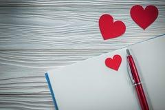 Taccuino rosso della penna a sfera dei cuori su istruzione del bordo di legno concentrata Fotografia Stock