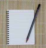 Taccuino a spirale realistico in bianco del blocco note con la matita su bam marrone Immagini Stock Libere da Diritti