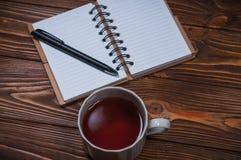 Taccuino su una tavola con una tazza e una tazza di tè immagine stock libera da diritti