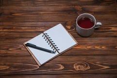 Taccuino su una tavola con una tazza e una tazza di tè fotografia stock libera da diritti