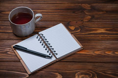 Taccuino su una tavola con una tazza e una tazza di tè immagini stock