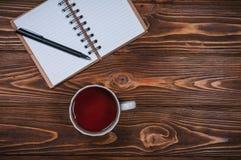 Taccuino su una tavola con una tazza e una tazza di tè Fotografia Stock