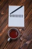 Taccuino su una tavola con una tazza e una tazza di tè immagine stock