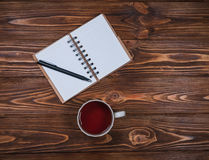 Taccuino su una tavola con una tazza e una tazza di tè immagini stock libere da diritti