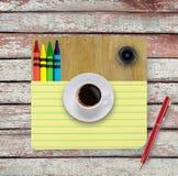 Taccuino, tazza di caffè, matite sulla tavola di legno fotografia stock